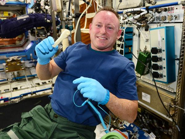 Commander Barry Wilmore holding the first 3D-printed tool produced on the ISS. Photo: NASA