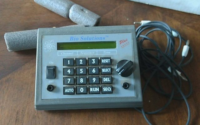 A device with a number pad, dials, and a small read out.